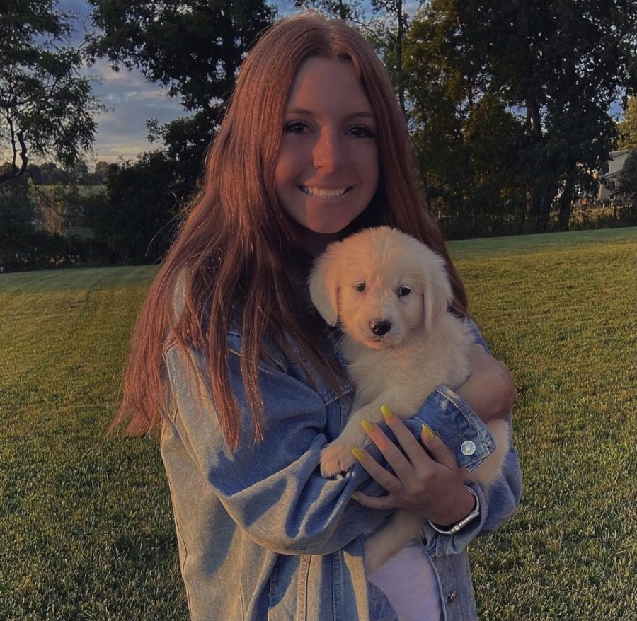 """Going for the Gold. Senior Colette Methling holds her Golden Retriever puppy, Toby. Her family got him in Ohio in September 2020. """"Toby is the real Heather,"""" Methling said, in reference to the popular song """"Heather"""" by Conan Gray."""
